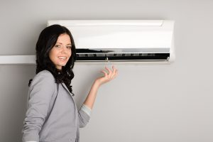 Beautiful smiling girl showing the air conditioner